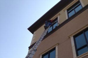 Man on ladder cleaning window