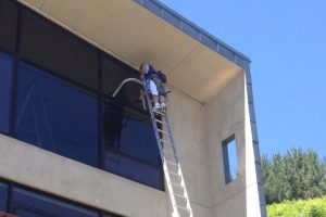 Man on ladder cleaning a window